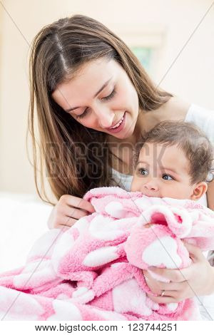 Happy mother and baby with blanket on bed at home