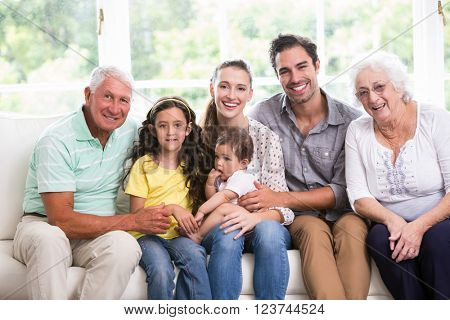 Portrait of smiling family with baby while sitting on sofa at home