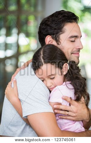 Daughter hugging father at home