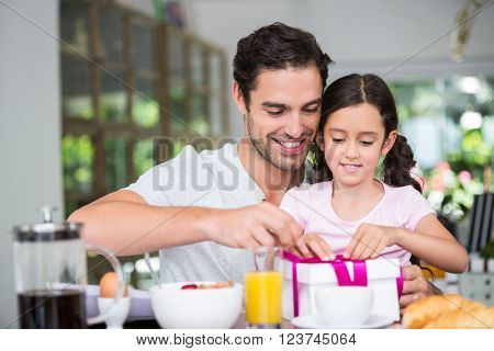 Smiling father and daughter opening gift boxat home