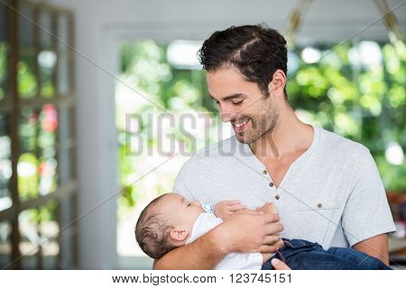 Smiling father carrying baby at home
