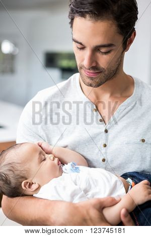 Father carrying sleeping baby at home