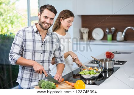 Happy young man helping woman in preparing food at home