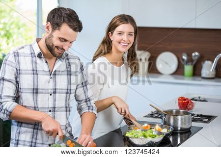 Cheerful young couple preparing food in kitchen at home