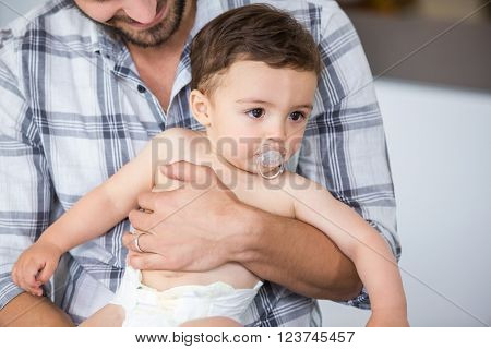 Close-up of father carrying son having pacifier in mouth