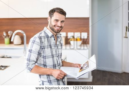 Portrait of happy young man holding newspaper while leaning on kitchen counter