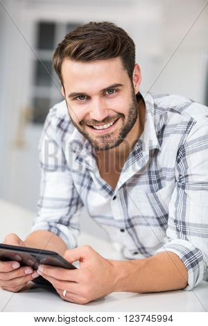 Portrait of handsome man using digital tablet while leaning on table