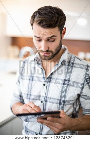 Close-up of confused young man using digital tablet in kitchen at home