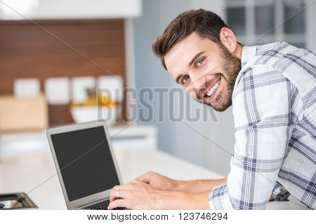 Portrait of happy young man using laptop while leaning on kitchen counter
