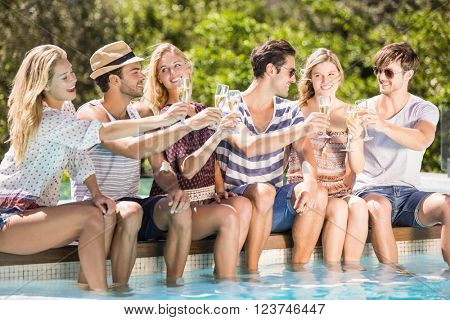 Group of happy friends toasting champagne glasses near pool