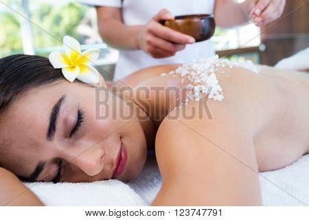 Woman enjoying a salt scrub massage at spa