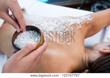 Woman enjoying a salt scrub massage at spa