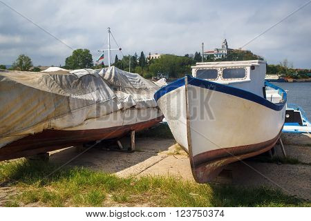 Boats on the shore at the water's edge. Close-up of old weathered boats hauled ashore. Selective focus.