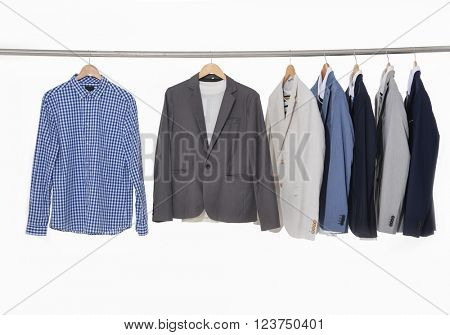 Row of men's suits hanging on the white background