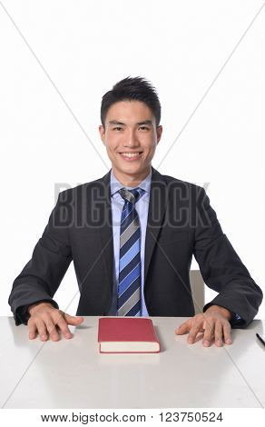 portrait of young businessman sitting with book