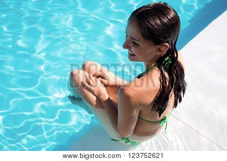 Portrait of smiling woman in swimming pool on a sunny day