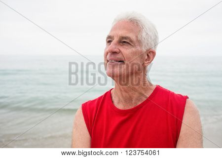 Thoughtful senior man looking away on beach on a sunny day