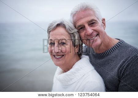 Happy senior couple embracing each other on the beach on a sunny day