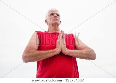 Senior man in lotus position on the beach