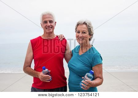 Portrait of smiling senior couple holding bottle while exercising on beach