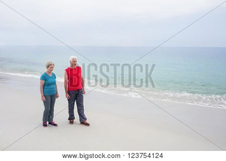 Senior couple standing on the beach on a sunny day