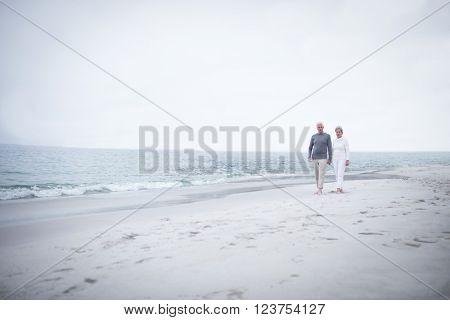Senior couple walking on the beach on a sunny day