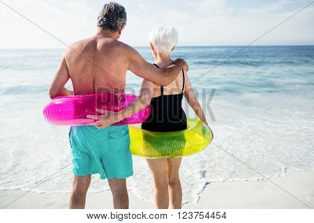 Rear of view senior couple in inflatable ring standing on beach