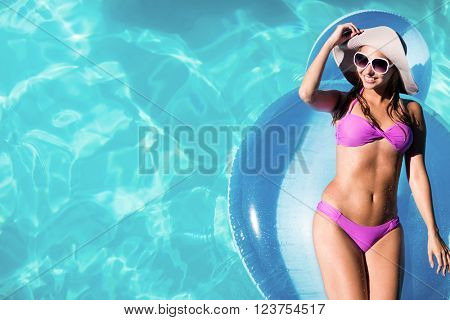 Woman relaxing on inflatable in swimming pool