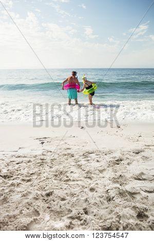 Rear view of senior couple enjoying on beach on a sunny day