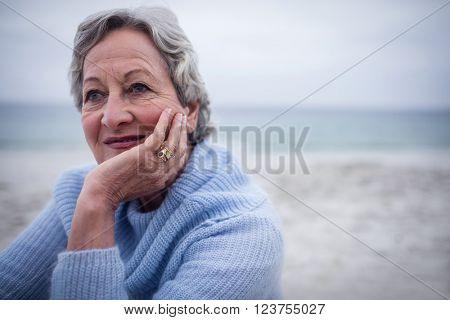 Thoughtful senior man sitting on the beach on holidays