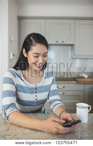 Happy woman typing a text message on her mobile phone in kitchen at home