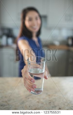 Young woman holding a glass of water in kitchen at home