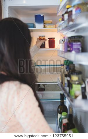Woman checking food in refrigerator at home