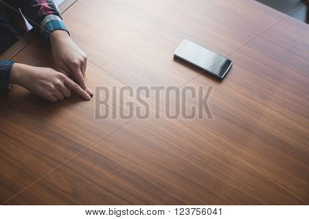 Woman placing her index fingers on a table near her phone