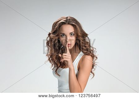 Portrait of young woman with shocked facial expression  over gray background. Girl broughting a finger to his lips for silence