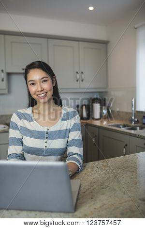 Portrait of young woman using a laptop in the kitchen at home