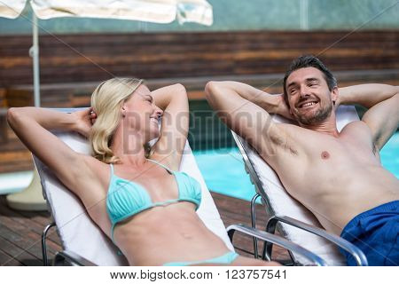 Couple talking while relaxing on a sun lounger near pool