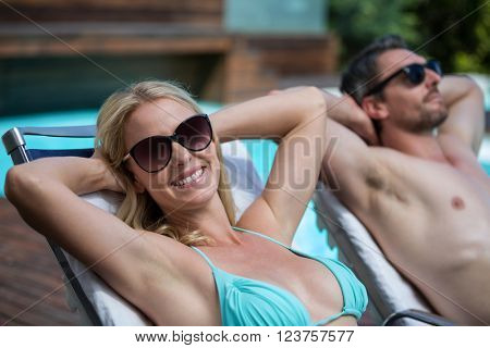 Couple wearing sunglasses and relaxing on a sun lounger near pool