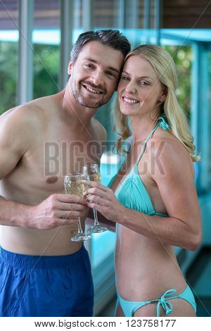 Portrait of couple holding a champagne glass while romancing near the pool