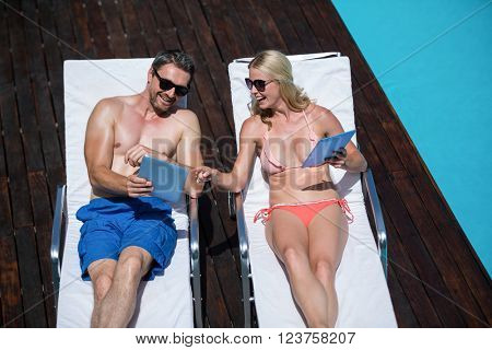 Cute couple using tablet and lying on deckchairs resting next to the pool