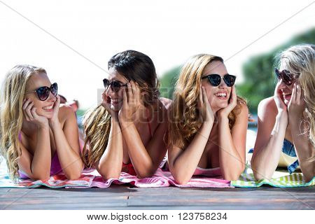 Group of friends lying near pool on a sunny day