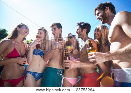 Group of happy friend holding beer bottles and glass of cocktail near pool