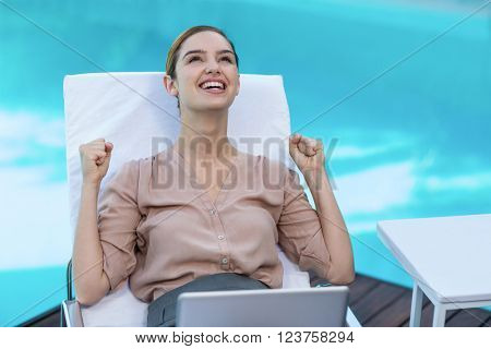 Excited woman relaxing on sun lounger with laptop near the pool