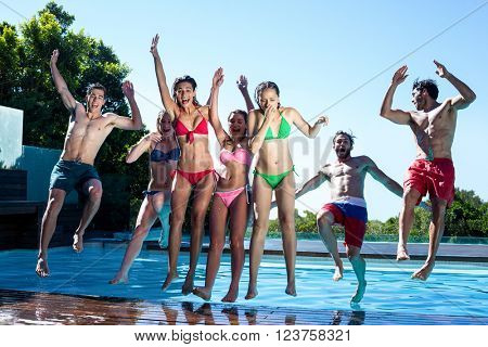 Happy friends jumping in swimming pool on a sunny day