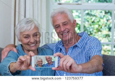 Smiling retired couple taking selfie at home
