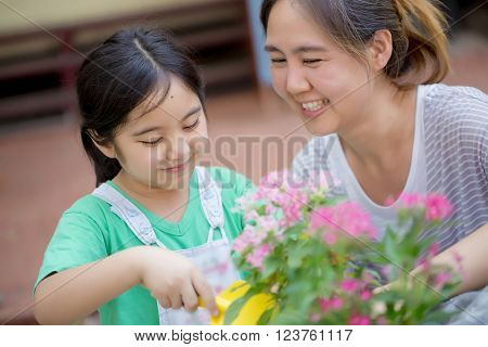Little Asian child planting flower with her mother
