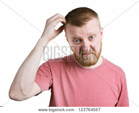 Young bearded man scratches his head hair