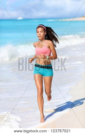 Fitness running runner exercising cardio with smartwatch activity tracker jogging barefoot on white sand beach living an active healthy lifestyle. Asian fit woman with wearable tech.