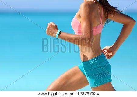 Wearable tech smart watch closeup, active woman wearing activity tracker bracelet on wrist. Runner girl running fast intense run outdoor on beach ocean background living a healthy life. Legs closeup.