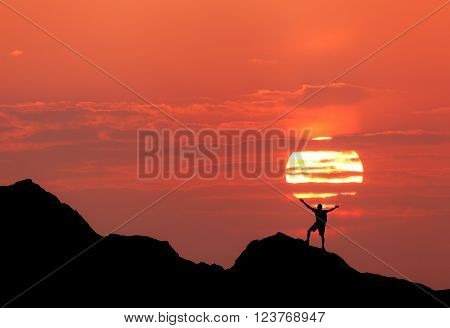 Sunset landscape with silhouette of a standing happy man with backpack and raised-up arms on the background of solar disk and red sky in summer. Travel background